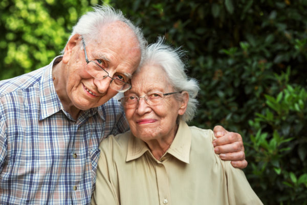 Elderly couple smiling and embracing