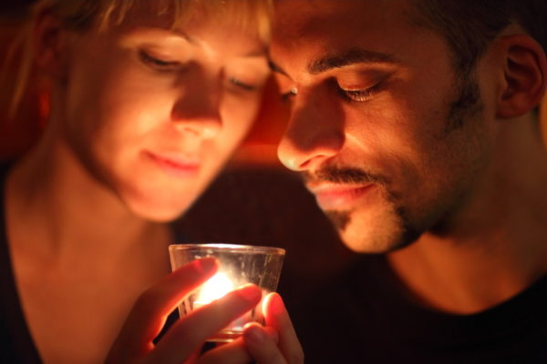 Loving couple maintaining intimacy over a flaming candle.