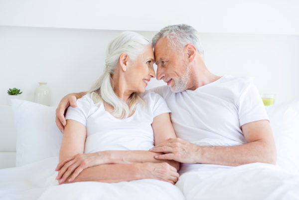 elderly couple in bed after having solved impotency erectile dysfunction (ED) problems